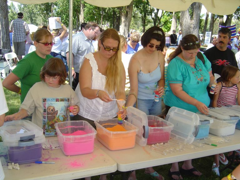 Image of guests creating sand art projects at an event.
